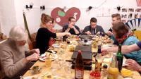 Sieben Personen sitzen um einen Tisch mit Raclette-Grill.