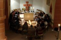 Menschen sitzen im Kreis vor einem Kreuz aus Kerzen