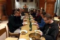 Mehrere Personen sitzen am Tisch mit einem Teller Suppe