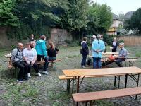 Vereinsmitglieder und Freunde an Tischen im Hof