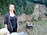 Junge Frau mit Grill im Hintergrund